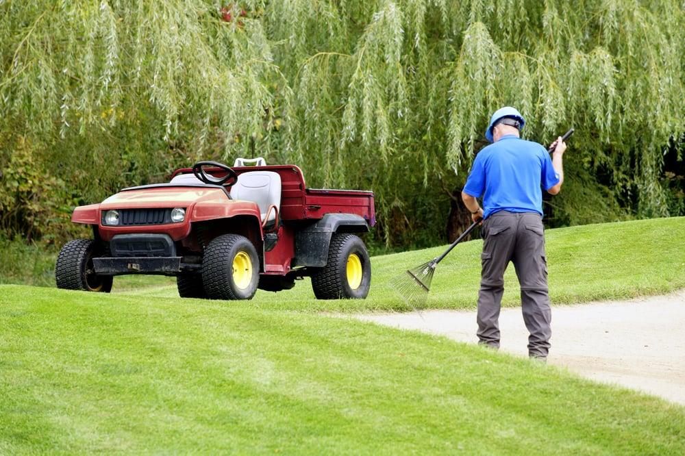 a golf course maintenance worker is raking a bunker
