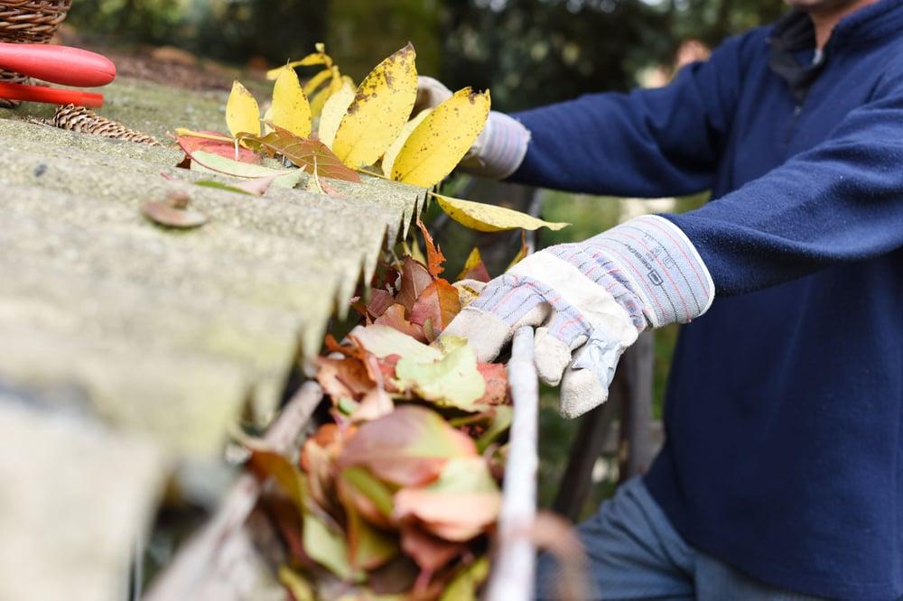 a maintenance technician cleaning gutters